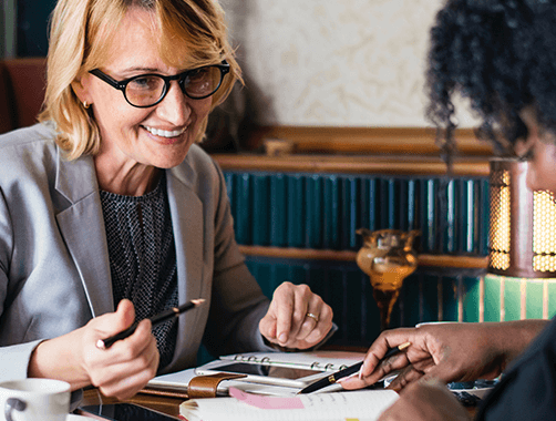 two professionally dressed smiling women reviewing documents